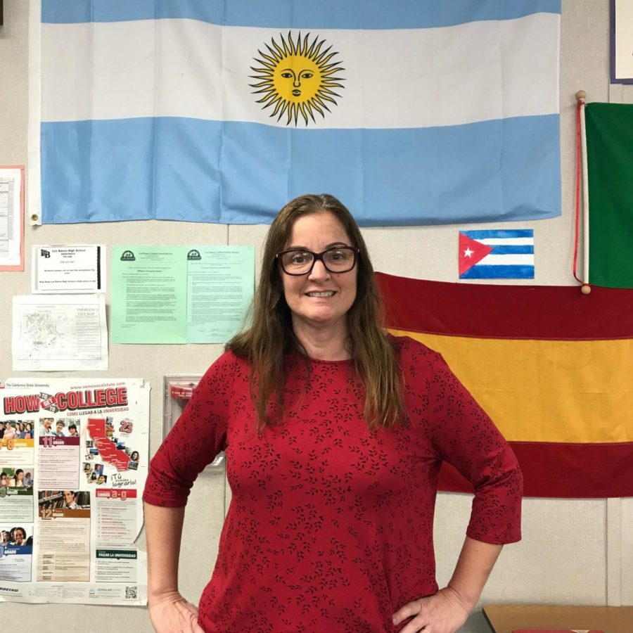 Mrs. Curutchague poses in front of her blue and white Argentina flag.