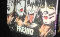 kiss band poses for concert banner