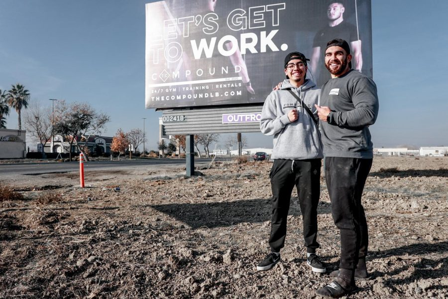 Gabriel Ortiz, (left), posing next to The Compound gym owner, (right), in front of a billboard.