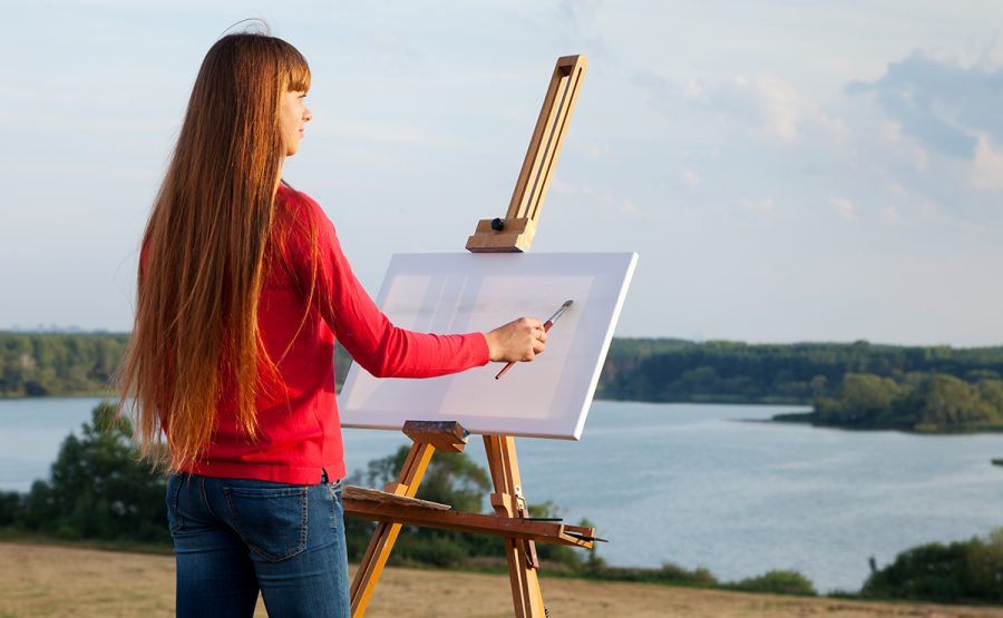 Girl begins a painting of the beautiful scenery.